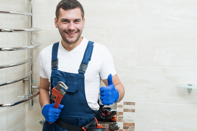 Cheerful plumber gesturing thumb up