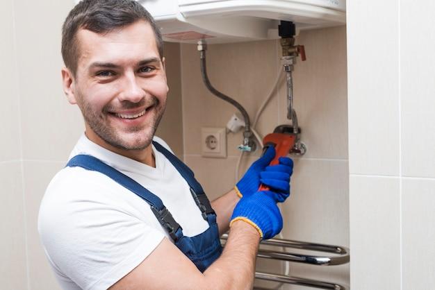 Cheerful plumber installing boiler