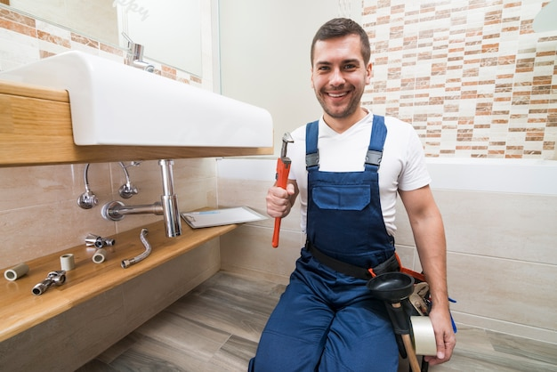 Cheerful plumber with wrench
