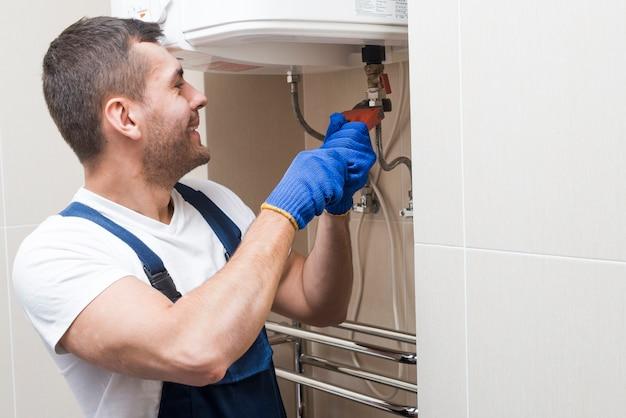 Веселый водопроводчик, работающий в ванной