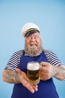 セーラー服の陽気な肉付きの良い男は、水色の背景にビールのガラスのマグカップを提供しています