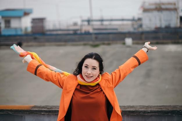 주황색 망토와 가지각색의 밝은 스카프에 검은 곱슬 머리를 가진 화려한 여자의 쾌활 한 초상화.