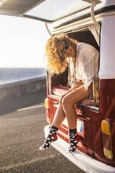 観光客の美しい女性の陽気な肖像画は、旅行して夏の代替休暇を楽しむ準備ができている彼女のバンの裏口の外に座っています-人々と放浪癖のバンライフライフスタイル