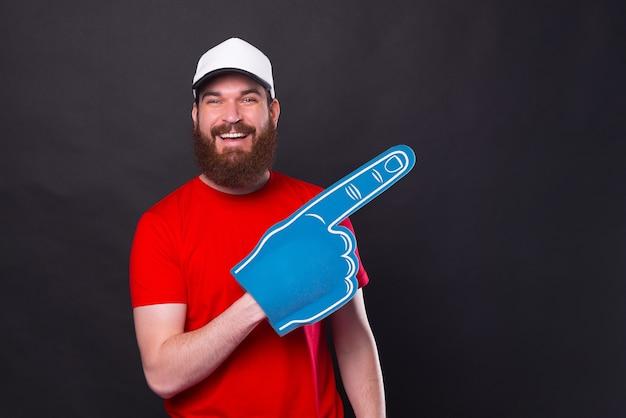 Веселый портрет молодого бородатого мужчины в красной футболке, указывающего прочь с веерной перчаткой из пенопласта