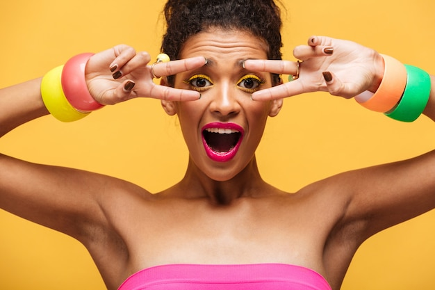 Cheerful portrait of young smiling mulatto woman with bright makeup showing peace sign with fingers on camera, isolated  over yellow wall