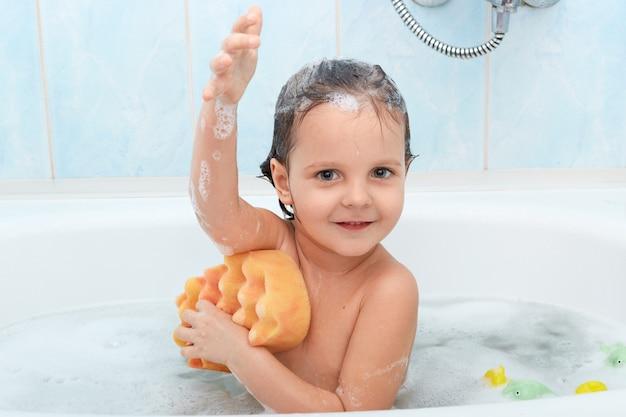 쾌활한 긍정적 인 사랑스러운 작은 아이가 목욕을하고 노란색 스폰지로 자신을 씻는