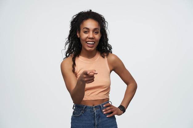 Веселая позитивная афроамериканка, смеется и указывает пальцем на вас