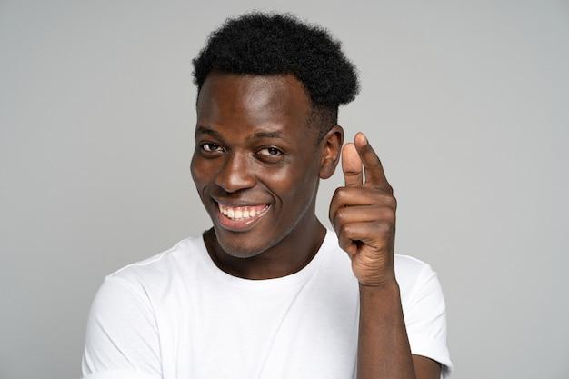 넓게 웃고, 당신에게 손가락을 가리키는 쾌활한 긍정적 인 아프리카 힙 스터 남자, 스튜디오 회색 배경