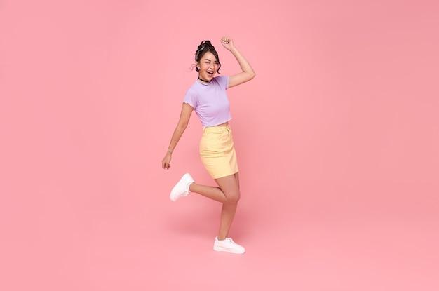 ピンクの背景に分離されたカメラを見て上げられた握りこぶしで空中にジャンプする陽気なポジティブなアジアの女の子。