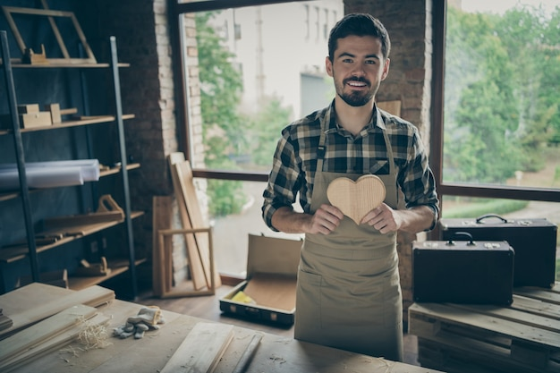 Cheerful positive attractive man holding wooden heart made by himself demonstrating his joinery talent