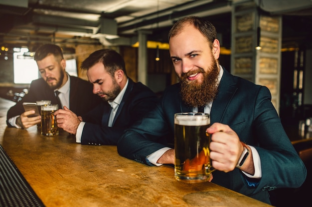 Cheerful and positive bearded man in suit look on camera. he smile and hold beer mug. other two young men sit behind.