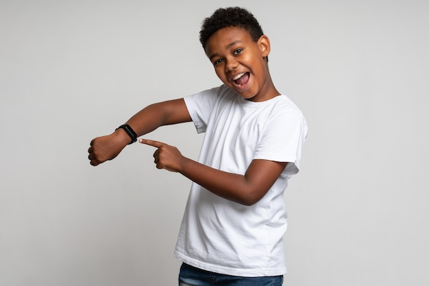 흰색 셔츠를 입은 쾌활한 긍정적인 소년은 손목시계를 가리키며 웃고, 새로운 스마트 시계를 보여주며 표시기를 확인합니다. 흰색 배경에 고립 된 실내 스튜디오 촬영