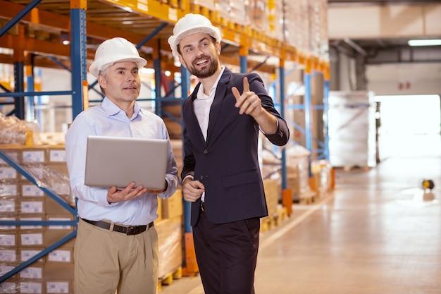 Веселый позитивный бизнесмен, указывая пальцем, объясняя свои идеи управляющему склада