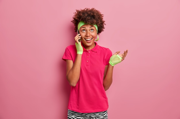 Cheerful positive curly haired teenage girl has telephone conversation