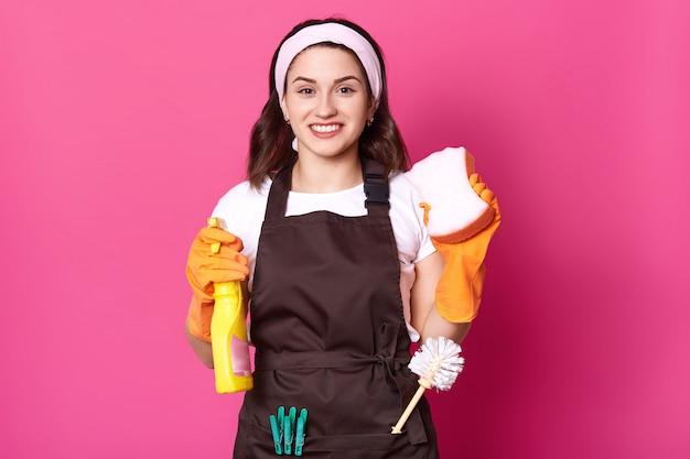 両手で手ぬぐいと洗剤を持ち、茶色のエプロンでトイレブラシと洗濯はさみを持ち、カジュアルな白いtシャツとヘッドバンドを身に着けている陽気な肯定的でかわいい主婦は喜んで見えます。