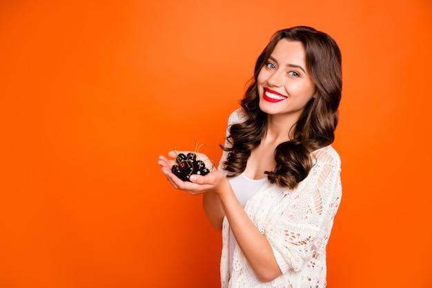 쾌활한 긍정적 인 귀여운 좋은 매력적인 예쁜 여자가 이빨 웃고 손으로 체리의 무리를 들고.