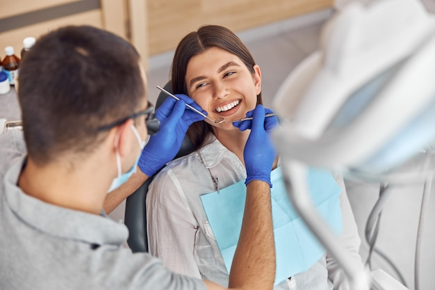Веселый позитивный стоматолог и клиент стоматологии. они смотрят друг на друга и улыбаются. клиентка сидит в кресле.