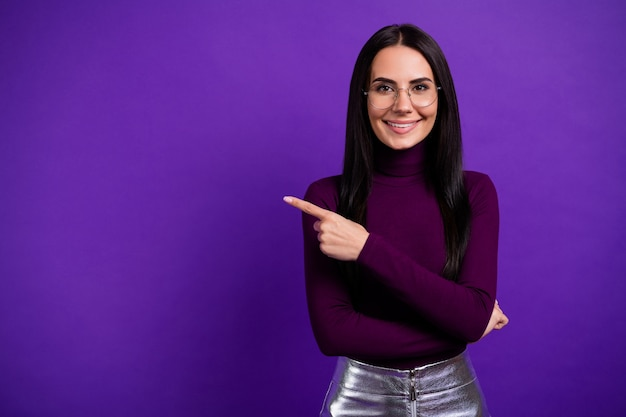 Cheerful positive girlfriend pointing into empty space isolated vibrant color wall