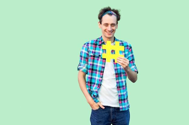 Жизнерадостный позитивный рад оптимистичный молодой человек в клетчатой рубашке, держащий большой желтый знак хэштега, концепцию социальных сетей. крытый, изолированный, студийный снимок, копия пространства, зеленый фон