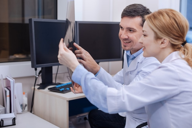 Cheerful positive good looking colleagues looking at the radiograph and smiling while having nothing serious to deal with