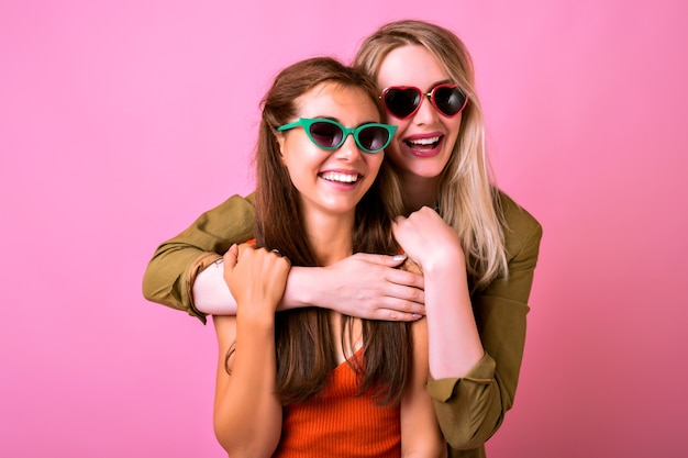 Cheerful positive indoor portrait of two funny blonde and brunette woman hugs and looking to each other