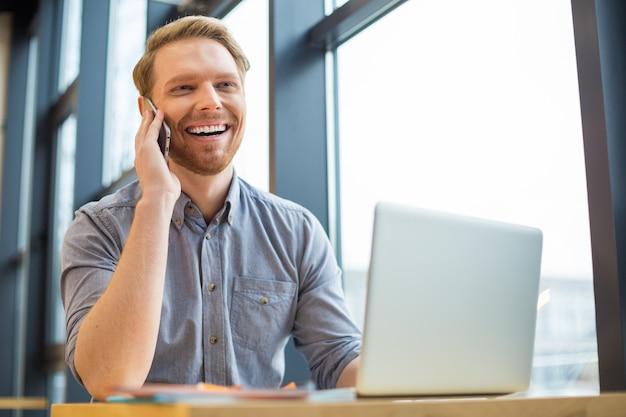 陽気で前向きなナイスマンが携帯電話を耳に当てて、楽しい会話をしながら笑う