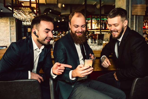 Cheerful positive and nice young businessmen sit in bar. they look at phone. first guy points on it. they smile.