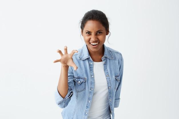 Allegro positivo giocoso divertirsi donna dalla pelle scura con capelli scuri vestita in camicia di jeans azzurro, mostrando i denti e gesticolando attivamente, cercando di spaventare qualcuno.