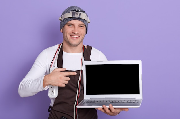 Cheerful positive radioman holding laptop with blank screen, making gesture, showing with forefinger, having double adapter and various cords on neck, standing with necessary equipment.