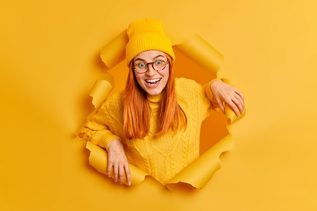 Cheerful positive redhead woman looks with glad expression has good mood wears yellow hat and sweater being pleased to pose for photo through paper ripped