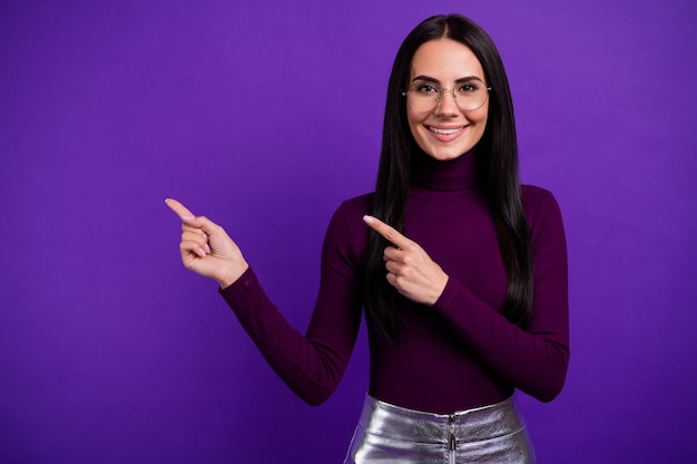 Cheerful positive  woman pointing into empty space smiling toothily isolated purple vibrant color wall