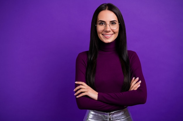 Cheerful positive woman with arms crossed, isolated on purple wall