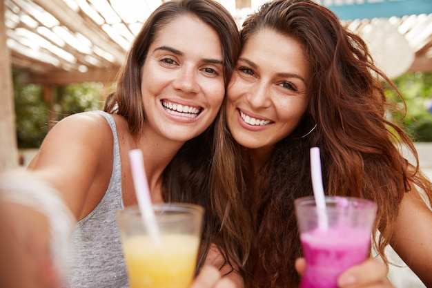쾌활한 긍정적 인 여성은 인식 할 수없는 장치의 카메라에 포즈를 취하고, 신선한 화려한 칵테일 음료로 셀카를 만들고, 야외 카페 인테리어에 앉아 있습니다.