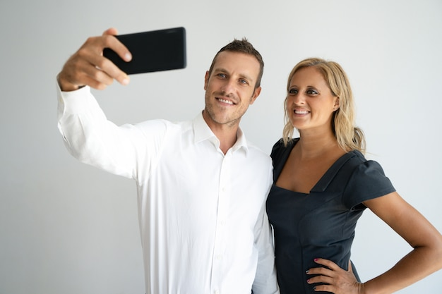 Cheerful positive young couple posing for selfie on smartphone.