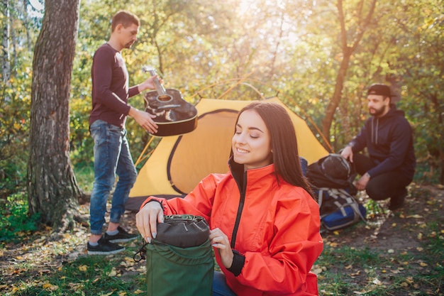 Cheerful and positive young woman smiles and holds backpack. she looks at it. first young man hold black guitar. another one sitting close to tent and backpack.