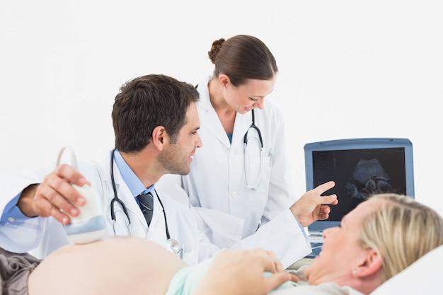Веселая беременная блондинка с ультразвуковым сканированием
