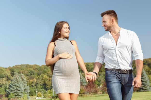 Веселая беременная пара гуляет в парке, держась за руки и счастливо улыбаясь
