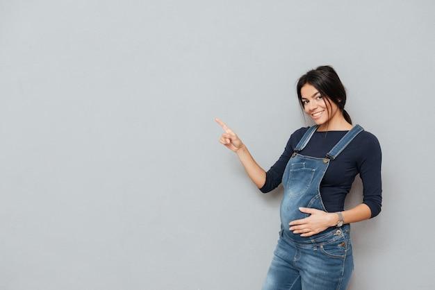 Веселая беременная женщина указывая.