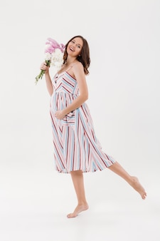 花を保持している陽気な妊娠中の女性。