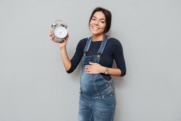 Веселая беременная женщина держит часы над серой стеной