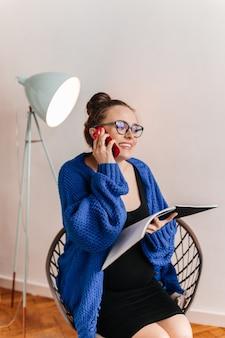 Веселая беременная женщина в синем кардигане разговаривает по телефону и держит ноутбук. девушка брюнет сидя на деревянном стуле.