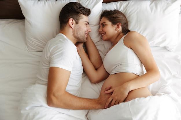 쾌활 한 임신 한 여자는 남편과 함께 침대에 놓여