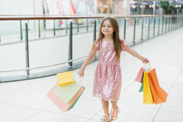 買い物袋と一緒に歩いている陽気な幼児の女の子。お店でポーズの買い物袋を持つ少女の笑顔。店舗でのショッピングのコンセプト