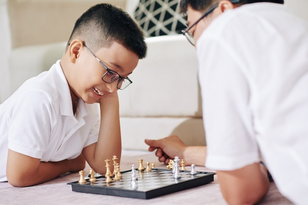 Cheerful preteen asian boy in glasses thinking about next move when playing game of chess with his dad