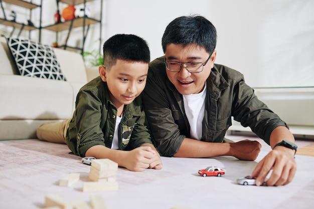 彼らが居間の床に横たわっているときに彼の父と一緒におもちゃの車で遊ぶのを楽しんでいる陽気なプレティーンの少年