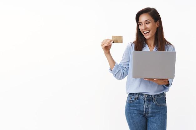 Веселая довольно взрослая женщина 30-х годов держит ноутбук, радостно смотрит на банковскую карту, довольная улыбка, делает покупки в интернете, покупает ноутбук, заключила хорошую сделку, довольная белая стена