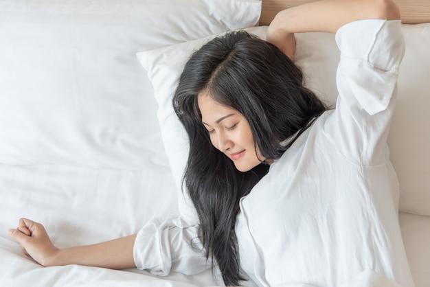 明るい可愛いアジアの女性の笑顔と幸せベッドで寝室