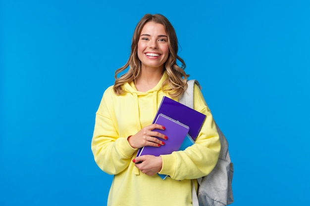 Cheerful pretty blond girl smiling, carry backpack and notebooks, papers for studying, learning new language at courses, standing joyful over blue wall