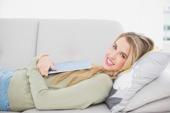 Cheerful pretty blonde holding her tablet lying on cosy sofa