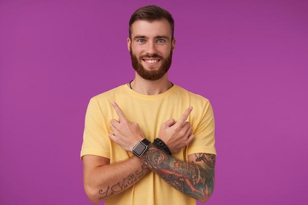 Веселый симпатичный голубоглазый бородатый мужчина с татуировками в повседневной одежде и фитнес-часах позирует на фиолетовом, с очаровательной улыбкой и скрестив руки